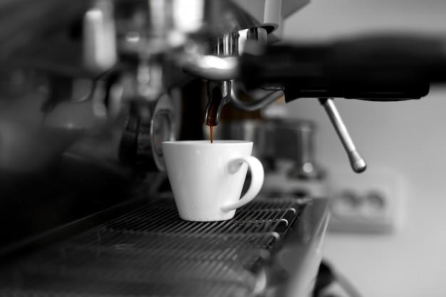 Uma máquina de café derrama café quente acabado de fazer em uma xícara branca