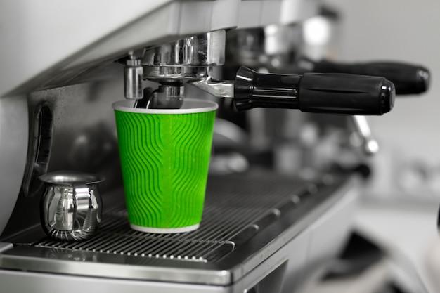 Uma máquina de café derrama uma bebida acabada de fazer em um copo de papel ecológico verde para um cliente. barista trabalha em uma cafeteria