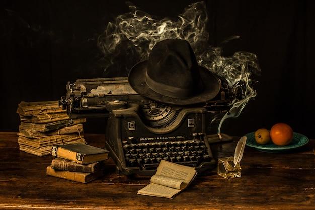 Uma máquina de digitar, um chapéu fedora e livros antigos em uma mesa de madeira