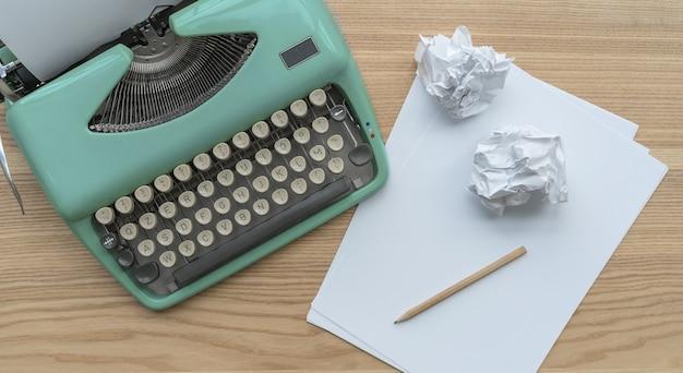Uma máquina de escrever azul vintage com estêncil de folhas de papel e bolas de papel na mesa de madeira