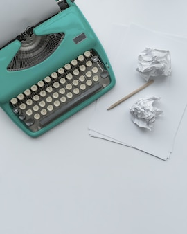 Uma máquina de escrever azul vintage com folhas de papel, estêncil e bolas de papel no fundo branco.