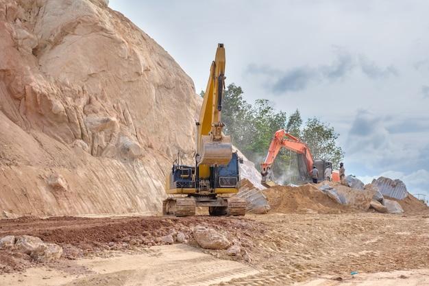 Uma máquina escavadora e uma máquina de elevação de pedra durante trabalhos de terraplenagem no canteiro de obras