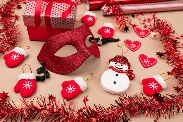 Uma máscara de máscaras brilhante no centro, cercada por presentes, enfeites, um boneco de neve, pequenas luvas vermelhas e rolos de papel de embrulho. . felicidade e alegria. decorações para a festa.