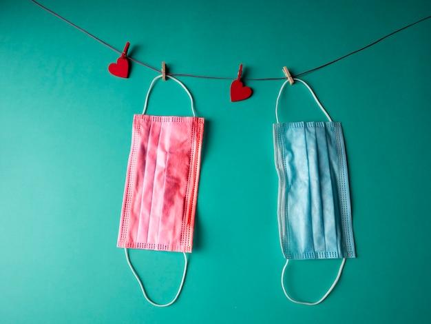 Uma máscara médica azul e vermelha que pesa em uma corda com dois corações vermelhos