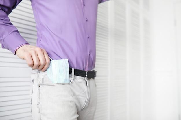 Uma máscara médica descartável sai de um bolso em vez de um guardanapo. um homem com uma máscara descartável de terno e jeans. proteção respiratória individual.
