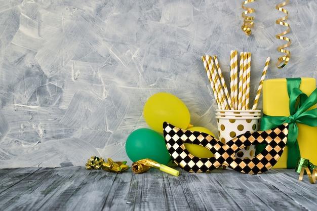 Uma máscara preta e dourada e vários acessórios para festas