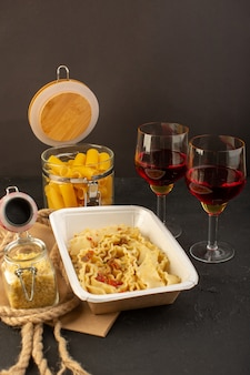 Uma massa italiana com ervas verdes secas dentro de uma tigela branca, juntamente com taças de massa italiana crua de vinho no escuro
