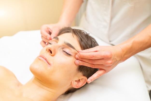 Uma massagem estética relaxante para uma jovem mulher com um rosto com olhos atraídos