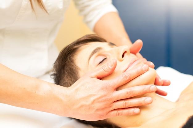 Uma massagem facial relaxante em um estudo estético