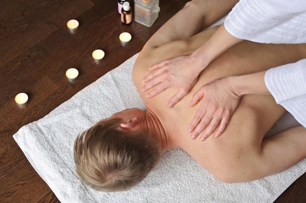 Uma massagista está fazendo uma massagem nos ombros para um homem