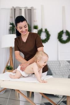 Uma massagista profissional faz uma massagem para um bebê. massagem infantil no sofá em um quarto moderno e aconchegante.