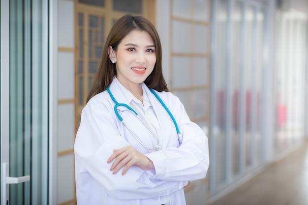 Uma médica asiática abraçou seu peito. vestindo uma túnica branca e estetoscópio