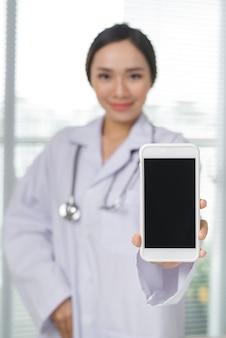 Uma médica bonita e sorridente com um estetoscópio mostrando a tela do smartphone sobre o fundo interior da clínica.