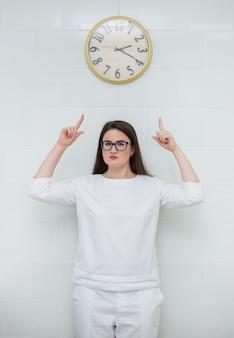 Uma médica com cabelo castanho e uma bata branca de médico se levanta e aponta para o mostrador do relógio