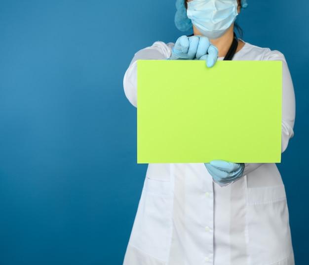 Uma médica com um jaleco branco, máscara descartável, óculos de proteção de plástico e boné está de pé e segura uma folha de papel verde em branco, um lugar para uma inscrição