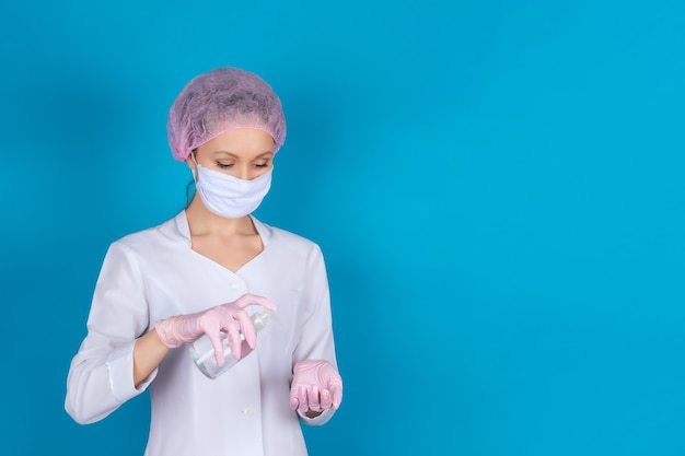 Uma médica com uma máscara médica, boné e luvas com um anti-séptico nas mãos em uma parede azul. isolar