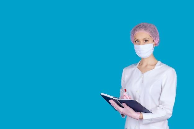 Uma médica com uma máscara médica e luvas com um bloco de notas nas mãos em uma superfície azul