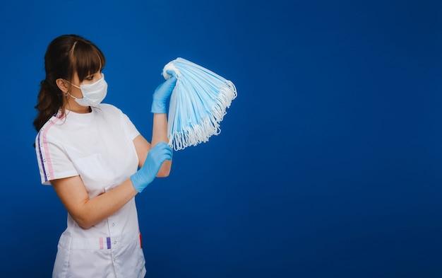 Uma médica com uma máscara médica em uma parede azul segura várias máscaras de proteção nas mãos