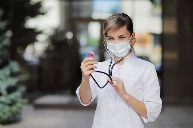 Uma médica com uma máscara médica facial com estetoscópio pronto para verificar os pulmões