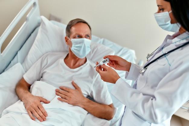 Uma médica com uma máscara protetora mede a temperatura de um paciente adulto do sexo masculino que está passando por reabilitação em uma enfermaria de hospital moderno durante o coronavírus ou epidemia de covid-19.