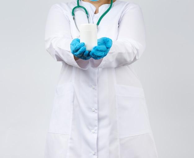 Uma médica de jaleco branco e máscara segura um frasco de plástico branco para medicamentos e pílulas