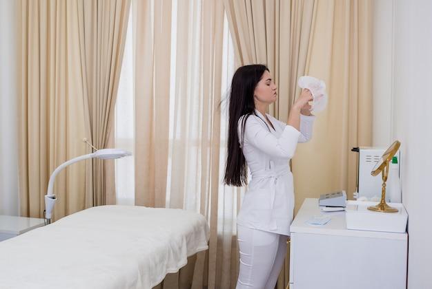 Uma médica de uniforme branco coloca um boné