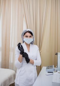 Uma médica de uniforme branco está de pé no consultório com luvas de látex pretas