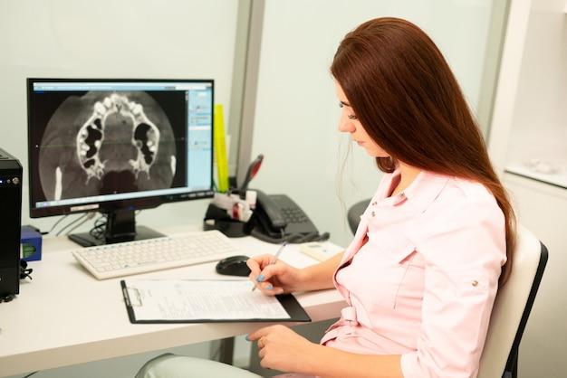 Uma médica dentista está sentada à mesa, em um computador, uma tomografia computadorizada da mandíbula. o médico está vestido com roupas profissionais.