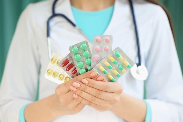 Uma médica detém um prato com comprimidos nas mãos dela. com profundidade de imagem de campo.