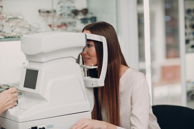 Uma médica e uma paciente fazendo exame oftalmológico de verificação de visão por refratômetro