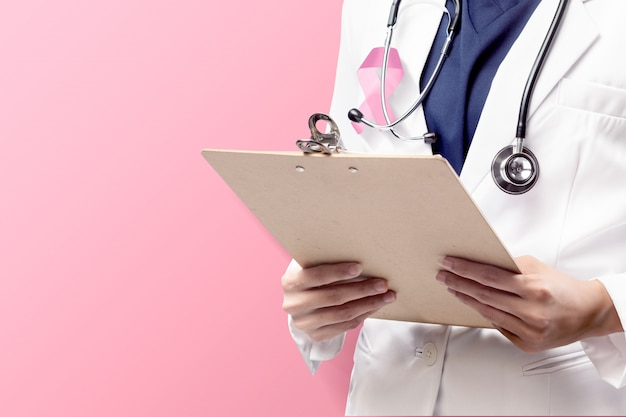 Uma médica em um jaleco branco com uma fita rosa e um estetoscópio segurando a prancheta com um fundo rosa