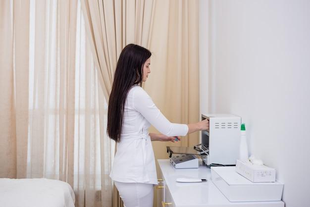 Uma médica em um uniforme branco esteriliza instrumentos