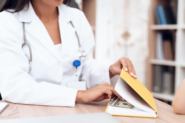 Uma médica esconde o dinheiro que o paciente lhe deu.