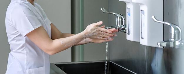 Uma médica lava bem as mãos com sabão em água corrente em uma pia de aço inoxidável. medidas de desinfecção necessárias