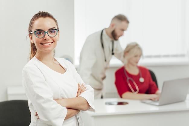 Uma médica morena de uniforme sorrindo