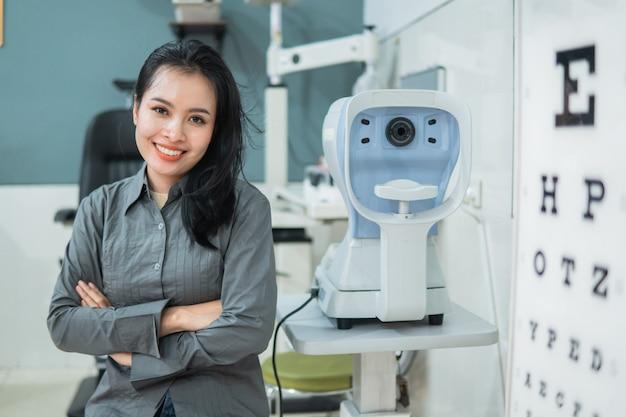Uma médica posando ao lado de um kit de exame oftalmológico localizado na sala de exames de uma clínica de olhos