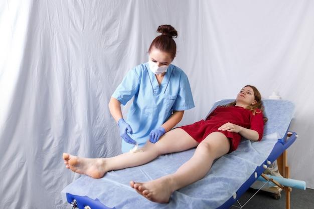 Uma médica realizando o procedimento de transferência de pasta de açúcar em um pé para uma jovem, plano geral