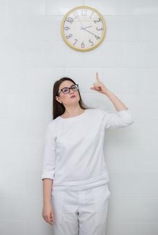 Uma médica usando óculos e um uniforme médico branco se levanta e aponta para o relógio