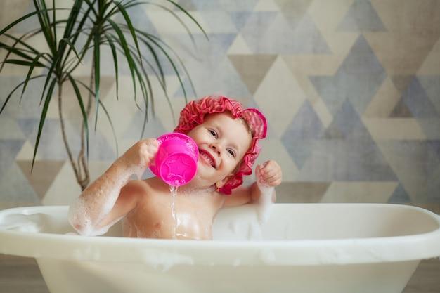 Uma menina 3-4 anos de idade toma banho em uma bela casa de banho em uma parede de luz. higiene infantil.