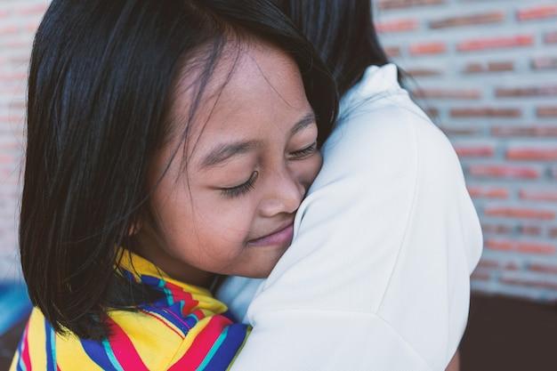 Uma menina abraça com a mãe, o conceito de mostrar amor e carinho na casa da família.