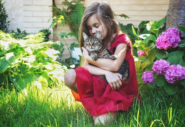 Uma menina abraça um gato