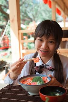 Uma menina adolescente comendo salmão don em um restaurante.
