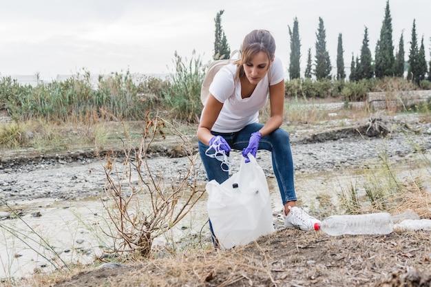 Uma menina agachada reciclando um pedaço de plástico