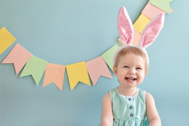 Uma menina alegre com um sorriso nas orelhas de coelho