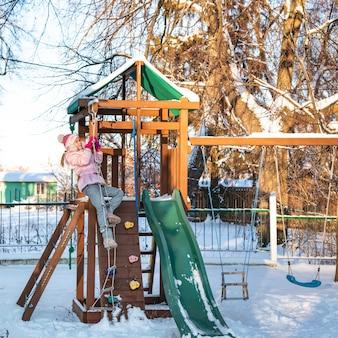 Uma menina alegre criança brincando no playground em dia ensolarado de inverno nevado.