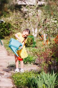 Uma menina alegre e sorridente em um vestido amarelo está regando brotos de plantas no quintal em um wa ...