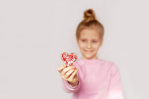 Uma menina alegre mantém pão de gengibre em forma de coração