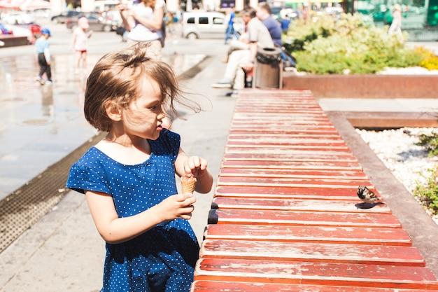 Uma menina alimenta pão para o pássaro, pardal, animais e crianças, sorvete, cidade e verão