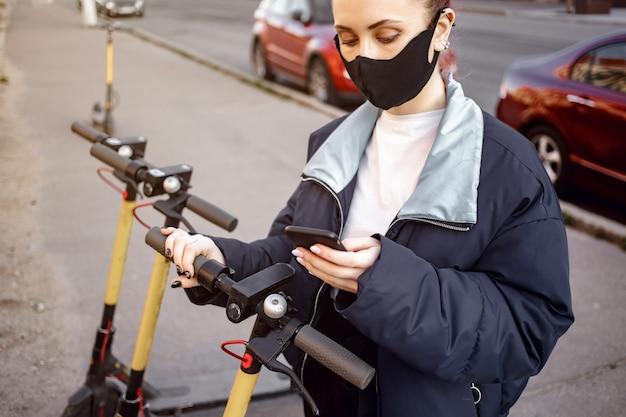Uma menina aluga uma scooter usando seu telefone