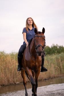 Uma menina andando a cavalo em um lago raso, um cavalo corre na água no sunse